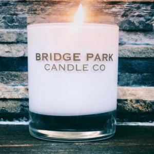 Bridge Park Candle Company lit candle in front of a wooden background