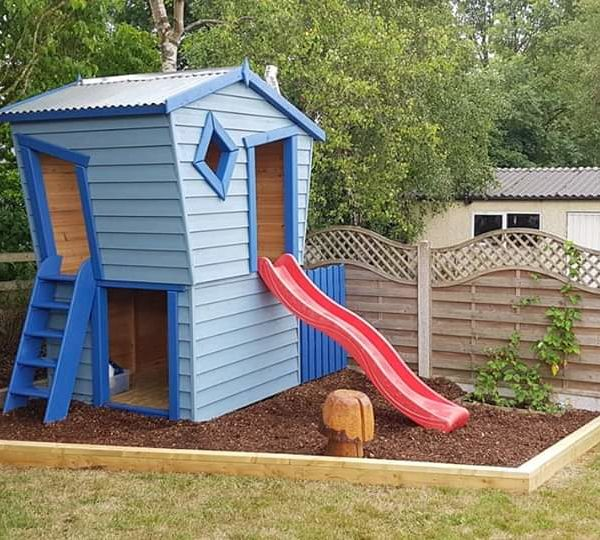 A custom made playhouse and slide with painted redwood cladding and a galvanised steel roof.