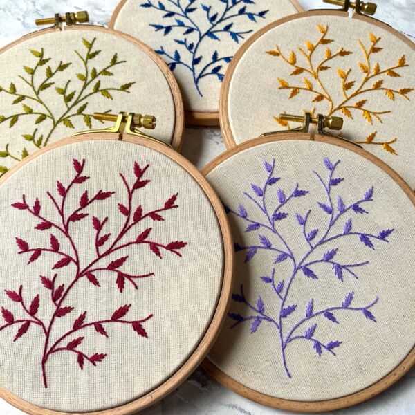 Five embroidery hoops hand stitched branches in different colours