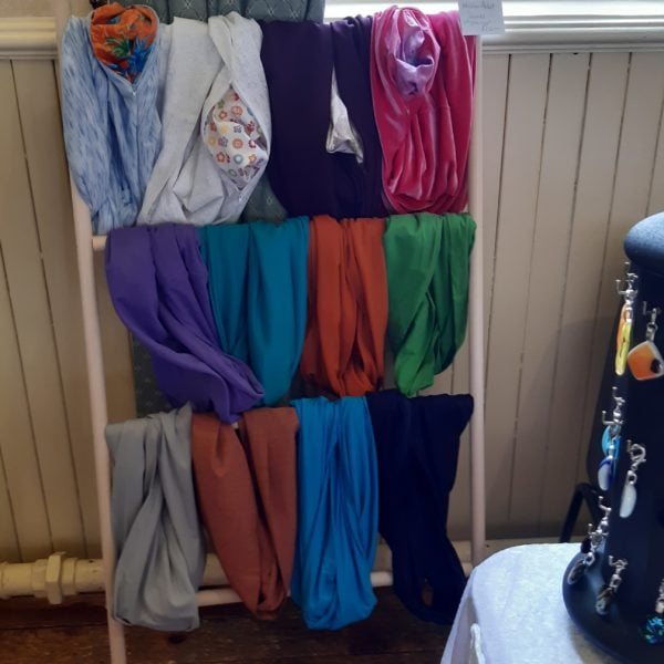 hanging rail displaying a number of different coloured scarves