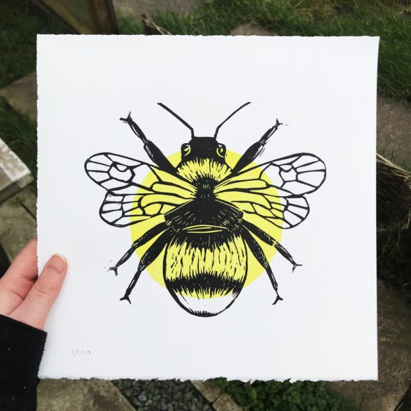 The Littlest Falcon - Bee lino print - Artists hand holding a yellow and black artwork of a bee.