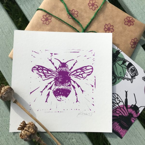 The Littlest Falcon - Bee Print Random Acts of Kindness - Linoprint of a Bee next to a notecard and handprinted wrapping papered gift.