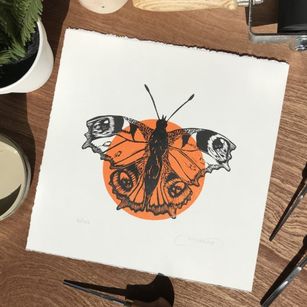 The Littlest Falcon - Butterfly lino print - Pictured against a wooden background with a plant and lino cutting tools. Art print.