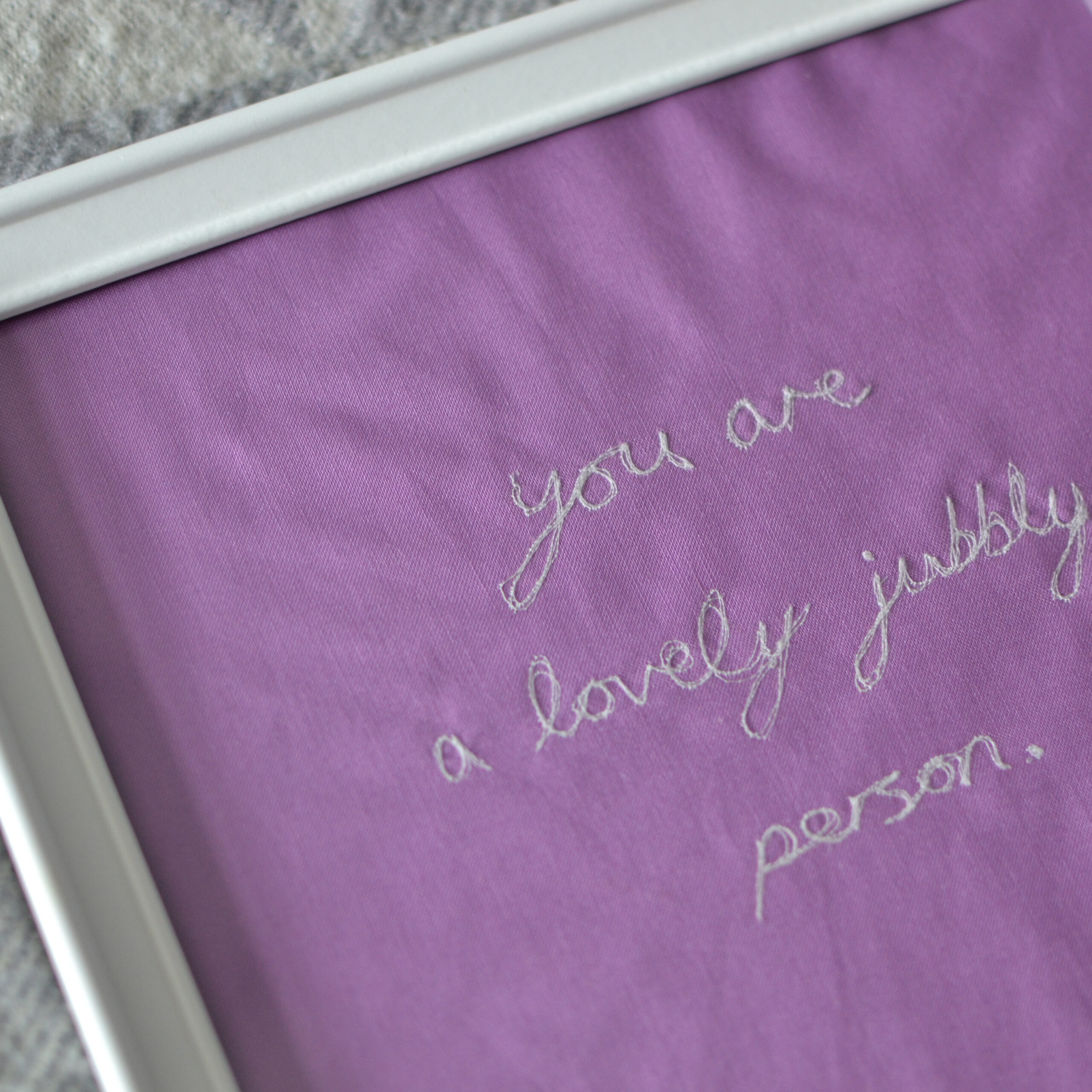 framed bright purple textile artwork by loaf & bear - embroidered text says 'you are a lovely jubbly person'