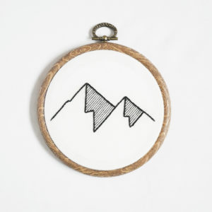 Black and white geometric mountain embroidery framed in a wood effect hoop