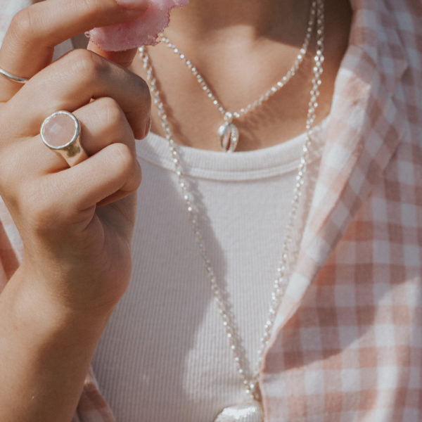 Scarlett eating candyfloss eating rose quartz aurora ring, cowrie shell necklace and maxi shell necklace