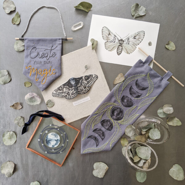 A variety of moon and moth themed papercuts, watercolours, paper sculptures, and embroidery