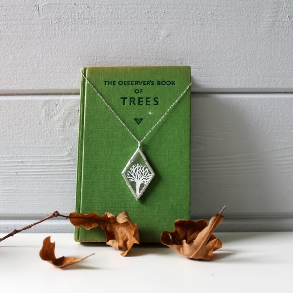 tree hand cut from white paper framed in a glass and plated silver diamond shaped necklace