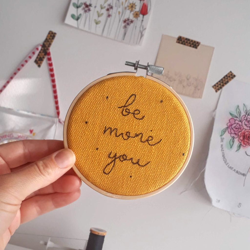 """Be more you embroidered ono a mustard coloured linen and set in a 4"""" wooden embroidery hoop"""