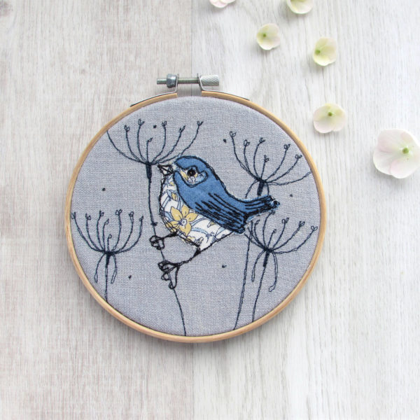 """Embroidered Countryside Bird in a 5"""" hoop on a French grey linen on a background of embroidered seedheads - Laced Wing Designs"""