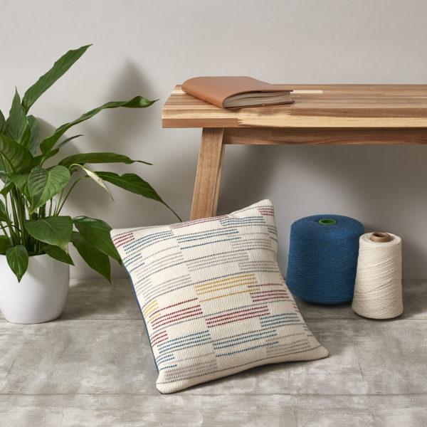 Hand-woven merino wool throw cushion in a linear pattern