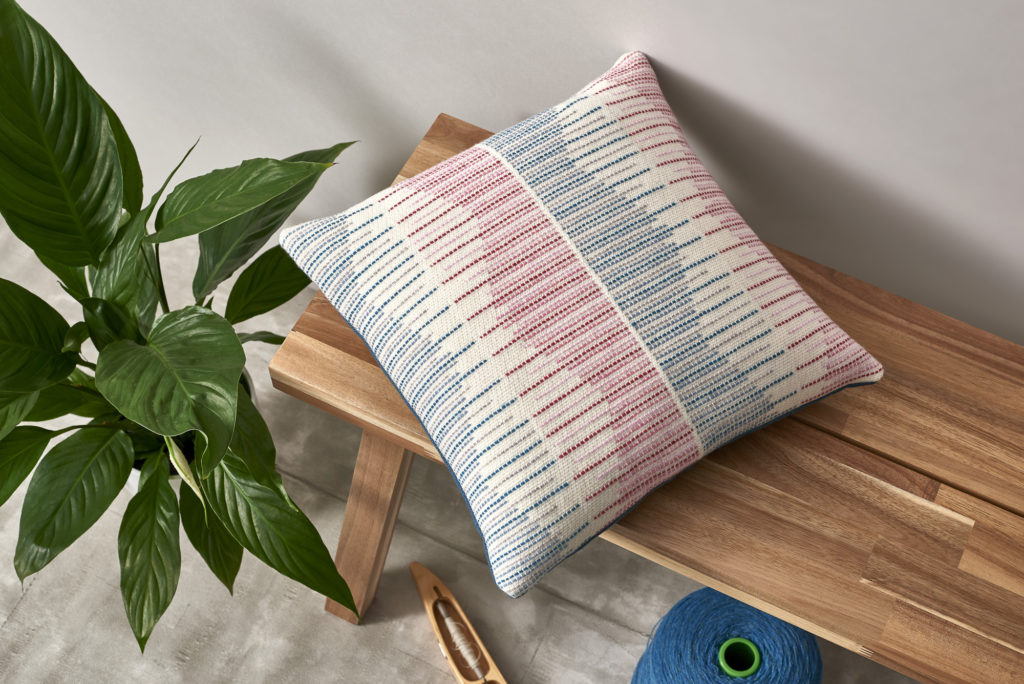 Hand-woven merino throw cushion in pink and blue