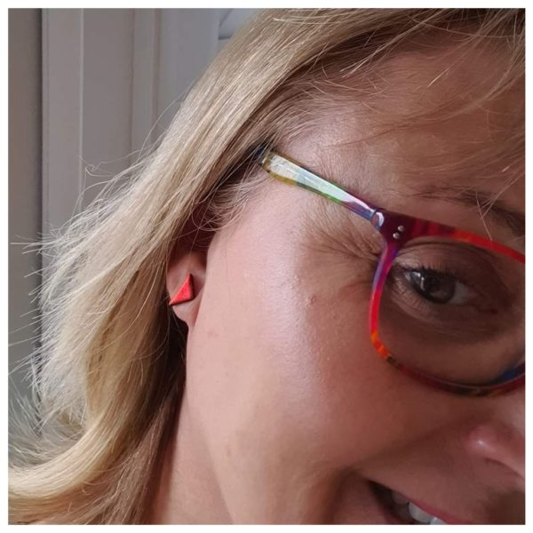 robyn coetzee glass designs, triangle stud earrings in red dichroic glass, someone wearing a pair of red triangle stud earrings and they match her red framed glasses