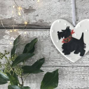 Hand Painted Ceramic Heart Of A Black Scotty Dog Wearing A Red Scarf With Holly And Berry Design Standing In The Snow
