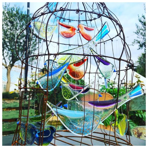 robyn coetzee glass designs, colourful glass birds in a wire cage, there are about ten glass birds hung inside a wire cage