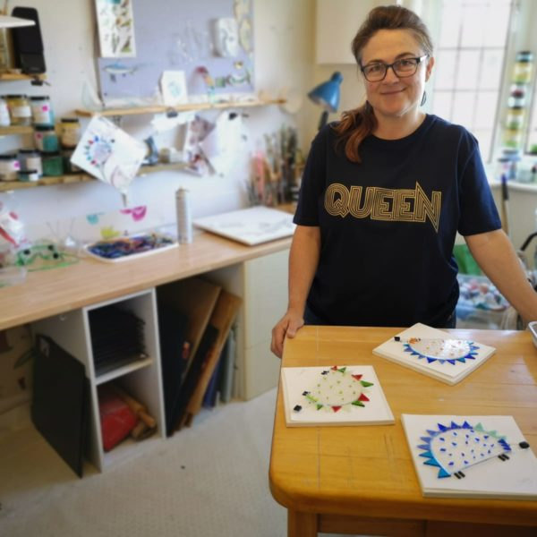 robyn coetzee glass designs, Robyn the artist in her glass studio, robyn standing in her studio next to some workshop hedgehogs