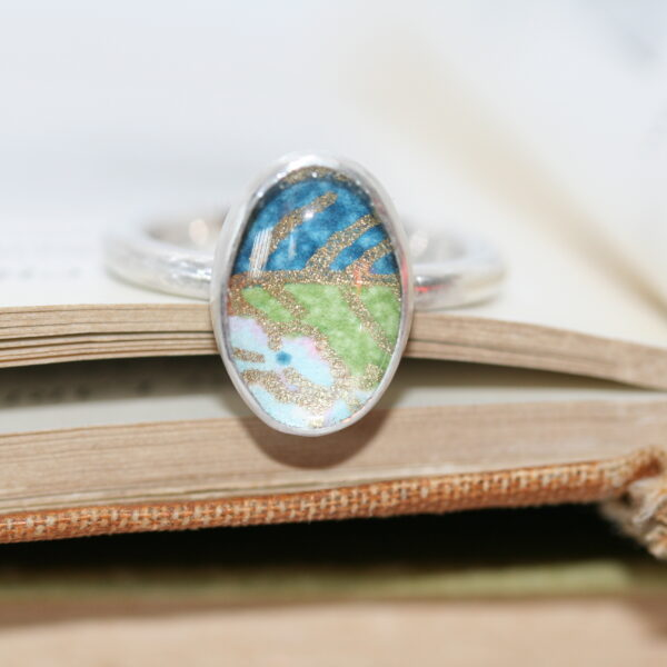 Platina jewellery, silver ring with patterned paper set under glass cabochon