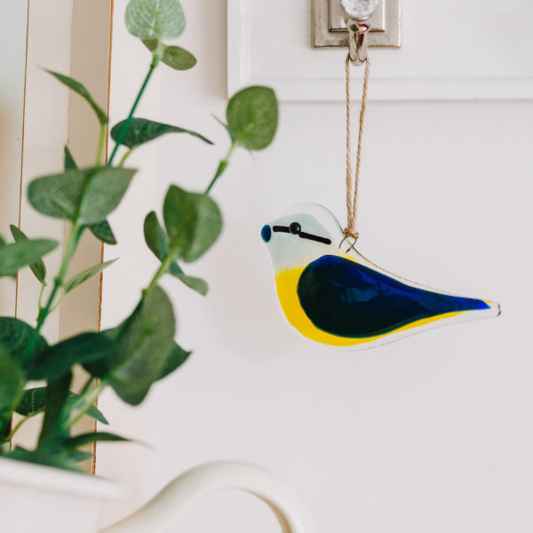 Glass at the Spinney, blue tit made in fused glass with yellow breast, blue wing and hanging on a hook