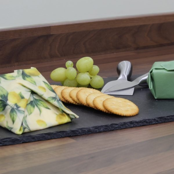 Sweet Bee Wraps UK green and lemon wax wrapped cheese board with grapes and crackers