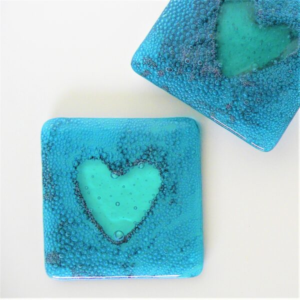 Glass at the Spinney, Sea Heart Coasters made of aqua coloured glass encasing hundreds of dark blue bubbles