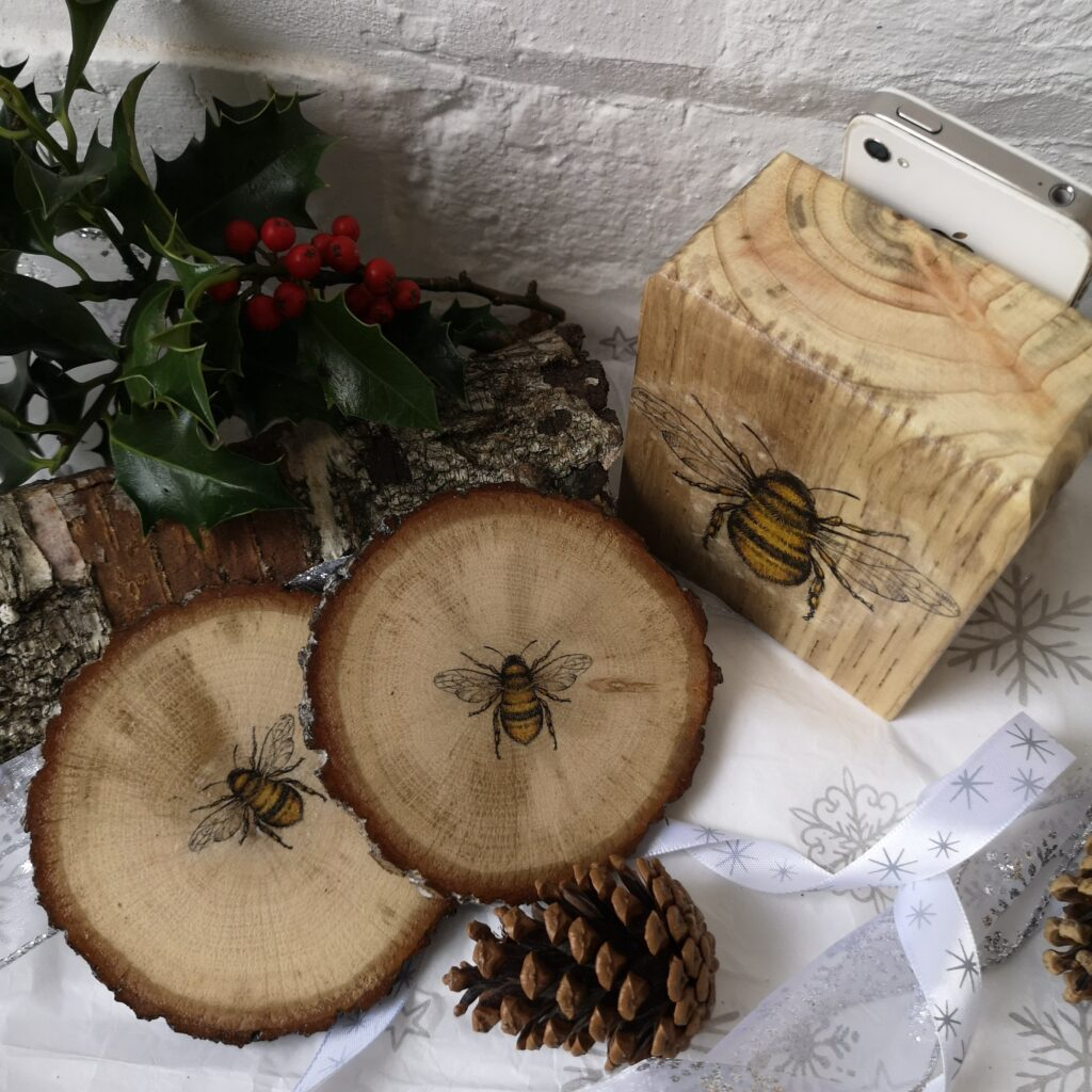 Ivy Upcycling Wooden Bee Gift Set all made from waste wood. Wooden Phone or Tablet stand decorated with lovely bee decoration plus 2 bark Bee decorated coasters.