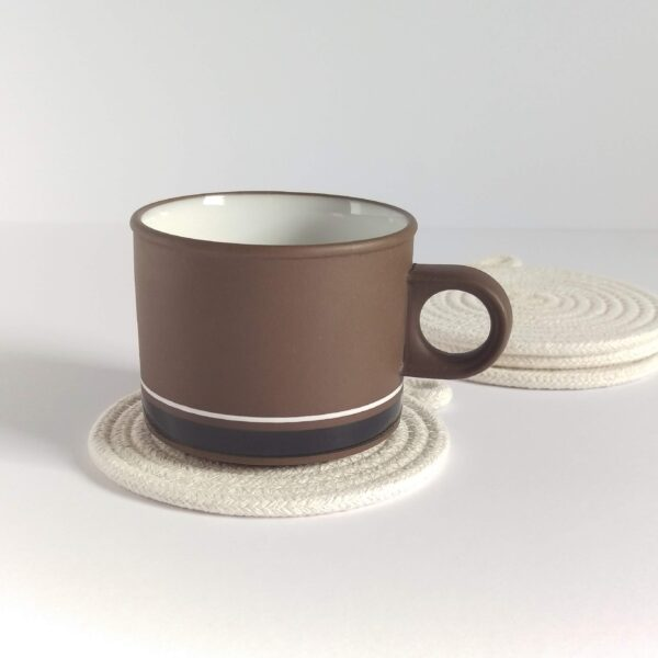 Against a white background a squat brown vintage coffee cup sits on a coiled cotton rope coaster