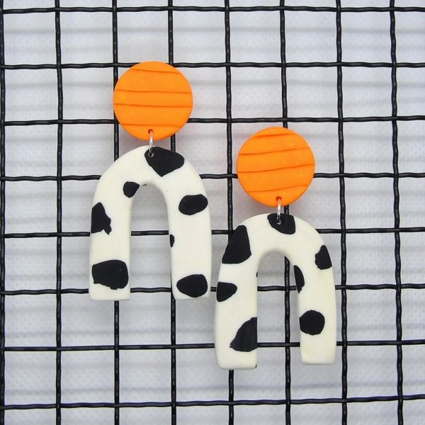 audrey and george cow print design with a neon orange top polymer clay earrings