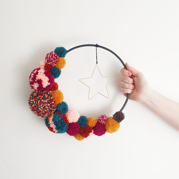 This is a navy painted bamboo hoop, with jewel toned pom poms creating a crescent moon shape. Hanging in the cetre of the hoop is a gold hanging star.