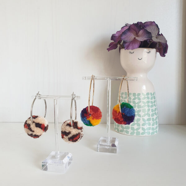 This image shows two pairs of pom pom earrings: the first is a neutral toned leopard print pattern and the other is rainbow colours.