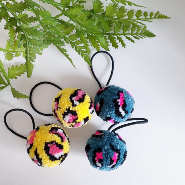 Two pairs of leopard print patterened pom pom hair bobbles, one pair is bright yellow with pink centred spots, the other is a denim blue, also with pink centres to the spots.
