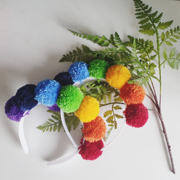 Two rainbow headbands, made with seven bright pom poms, on a white bases