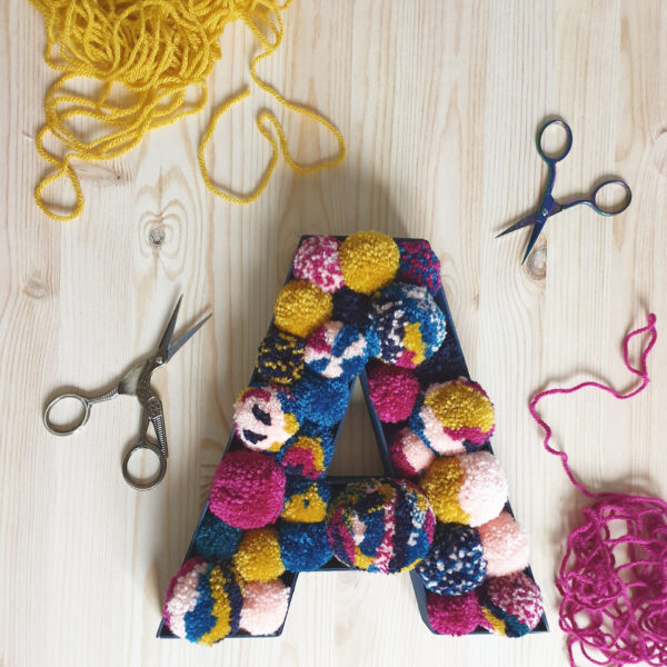 A wooden fillable letter, painted navy and filled with a collection of jewel toned pom poms in different shapes