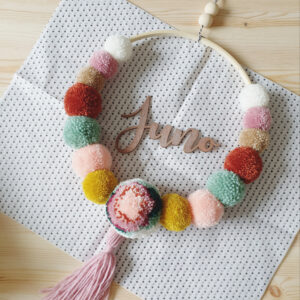 A bamboo hoop with pom poms in neutral tones surrounding a large floral pom pom with tassel. It has been personalised with the name 'Juno' made from wood and handpainted bronze. it is resting on polka dot tissue paper.