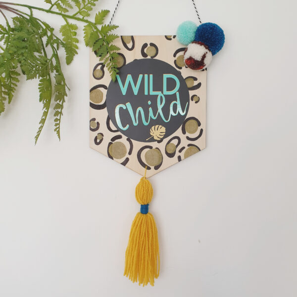 A wooden pennant with a handpainted leopard print background. This then has vinyl lettering with ,wild child, written in mint writing. It is completed with a trio of pom poms and a large tassel at the bottom, and hung using baker's twine.