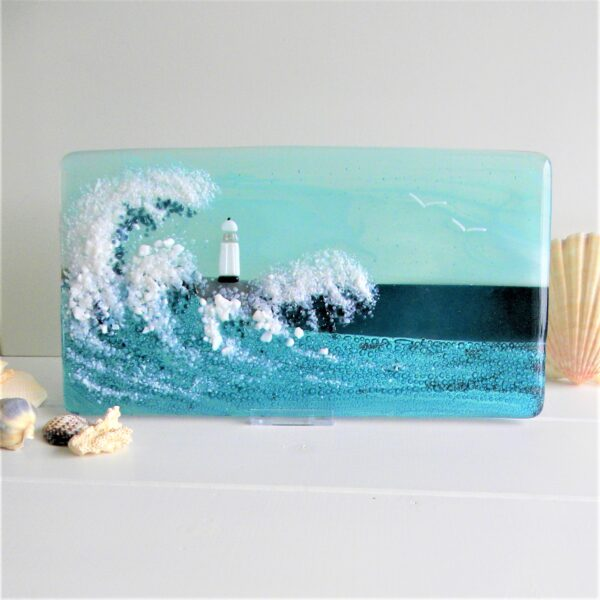 Glass at the Spinney, Storm at Sea in aqua. Glass panel depicting giant waves crashing over lighthouse during a storm. Displayed on white table with sea shells