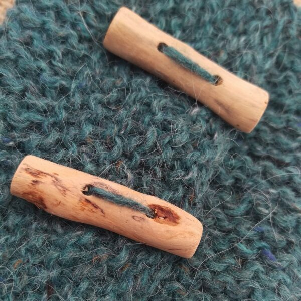 A close up of two pale driftwood buttons on soft turquoise knitting