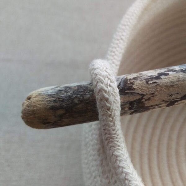 Close up of the end of a driftwood handle on a coiled rope bowl