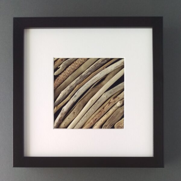 Against a grey background a square black frame with a diagonal arrangement of driftwood.
