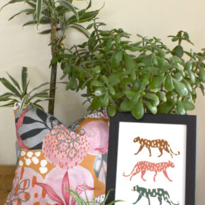 Megan Rose Designs, Pink Botanics cushion and 3 Jags print, pink and mustard colourful botanic cushion with framed wall art print with yellow, ochre, pink and green leopards, in front of house plants and succulents