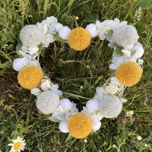Pom Pom Petite, White wicker heart wreath with mustard, grey and white pom poms and faux foliage and faux white flowers.