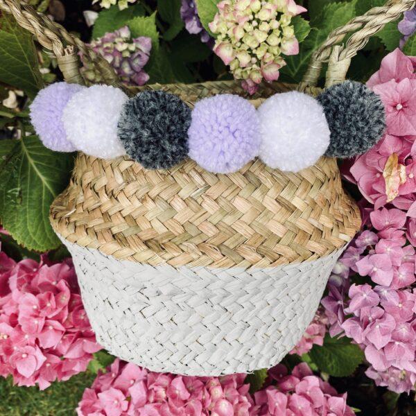 Pom Pom Petite, Grey and natural seagrass basket with lilac, white and dark grey pom poms.