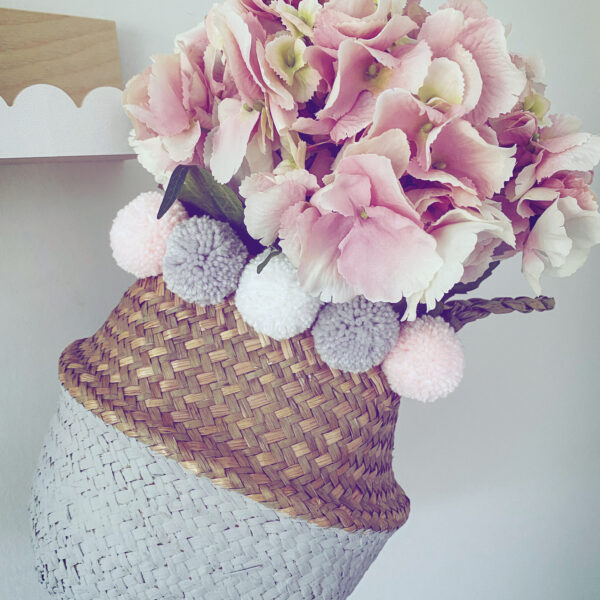 Pom pom petite, grey and natural seagrass basket with grey, white and pastel pink pom poms.