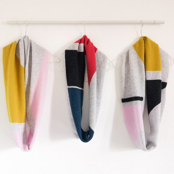 Lyndsey Currie - Knitted Accessories, Three Intarsia colour blocked snoods. Light grey, pink and piccalilli snood, Light grey, charcoal, blue and hot pink snood, Light grey, piccalilli, pink and charcoal snood. Colour blocked circle scarves, 100% high quality lambswool