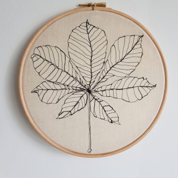 "Gemma Rappensberger Leaf illustration using free motion machine embroidery in black thread on calico displayed in a 7"" wooden embroidery hoop"