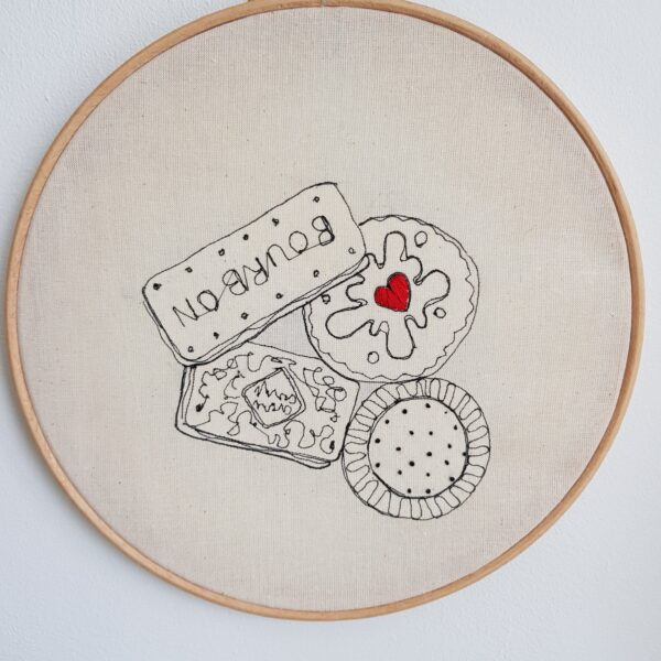 "Gemma Rappensberger Biscuits illustration free motion machine embroidery in black thread with red hand embroidery on calico in a 9"" wooden hoop."