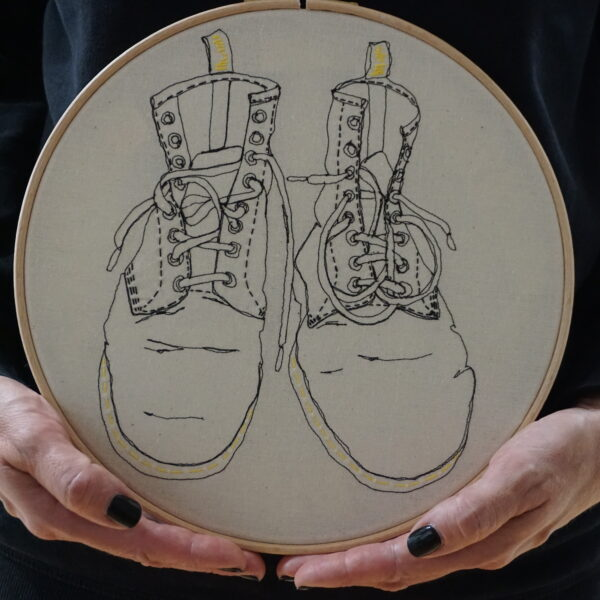 "Gemma Rappensberger Dr Martens Boots illustration in free motion machine embroidery in black thread with yellow hand embroidery details on calico, displayed in a 10"" wooden hoop, held by Gemma Rappensberger."