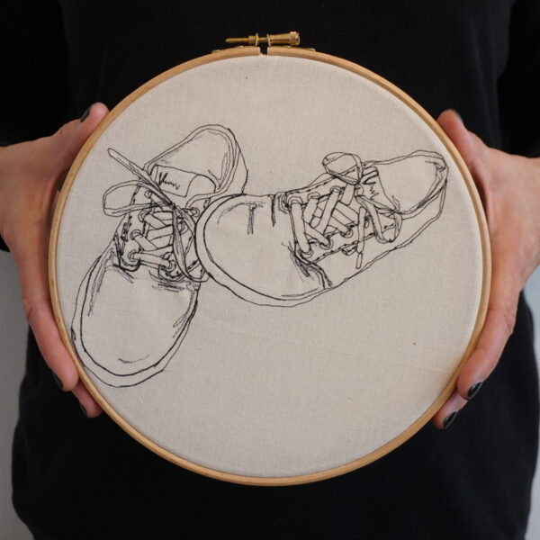 "Gemma Rappensberger Vans trainers illustration using free motion machine embroidery of Vans trainers in black thread on calico displayed in a 9"" wooden embroidery hoop, being held by Gemma Rappensberger"