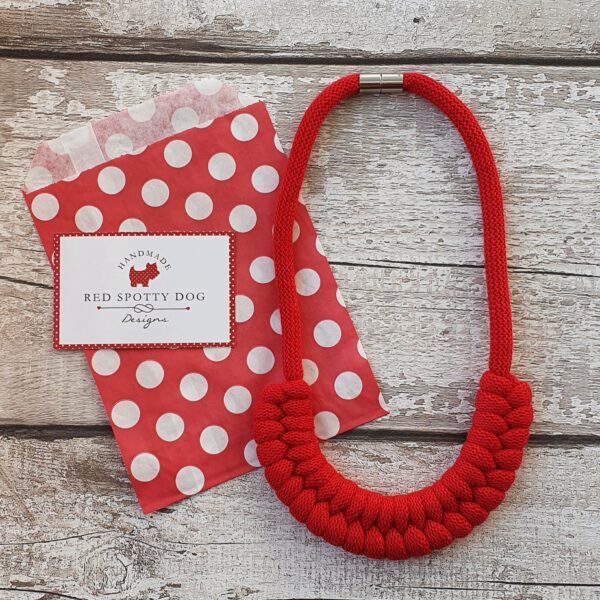 red Jayne style knotted necklace lay onto of red spotty paper bag abd business card