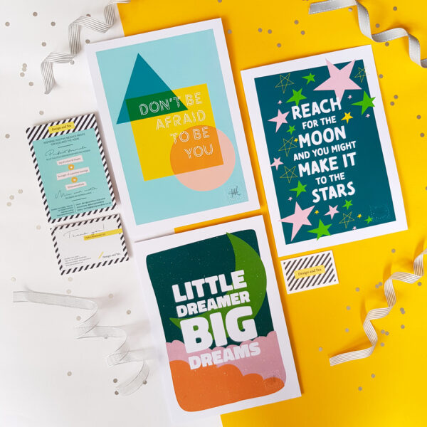Design and Tea, flat lay of set of three colourful inspiring typographic prints including 'Don't be afraid to be you', 'Reach for the moon and you might make it to the stars' and Little Dreamer Big Dreams' on a yellow background in colours green, mint, yellow, orange and pink.
