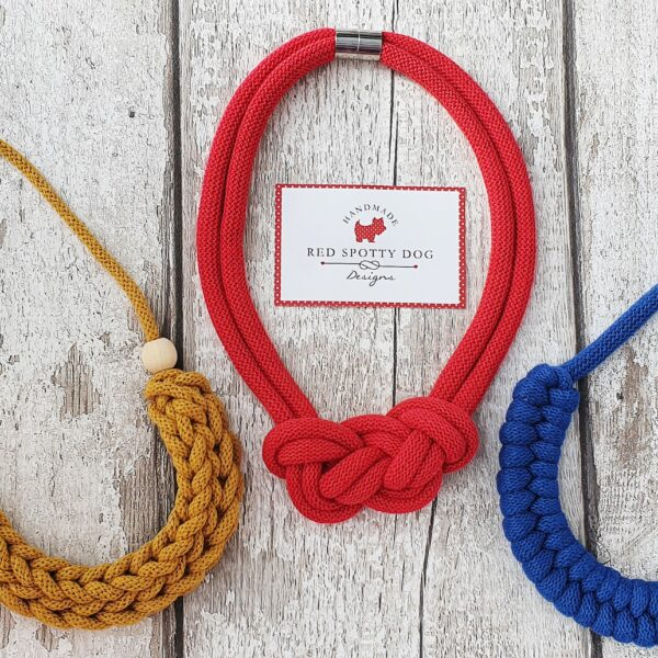 three knotted necklaces in primarily colours red blue yellow mustard flat lay